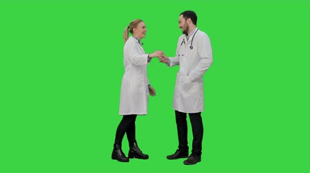 yanliŞ : Funny male doctor kidding on female nurse give a false hi five on a Green Screen, Chroma Key.