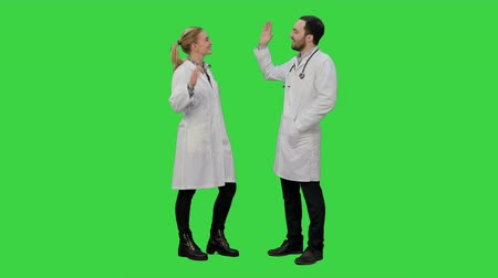 palmas das mãos : Young medical students give each other five after exam on a Green Screen, Chroma Key. Vídeos