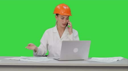 mimar : Woman in orange hardhat calling the phone discussing constraction plan on a Green Screen, Chroma Key.