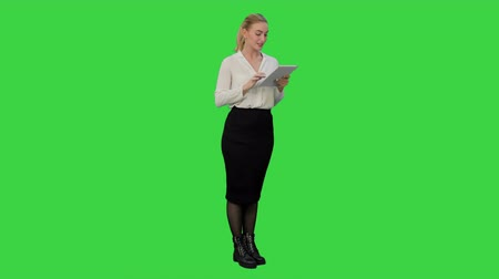 читатель : Concentrated young businesswoman using digital tablet present a project on a Green Screen, Chroma Key. Стоковые видеозаписи