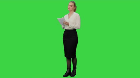 suporte : Attractive business woman makes some calculations and writes them down on paper on a Green Screen, Chroma Key.