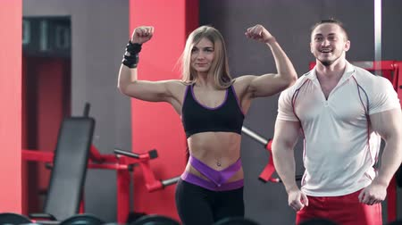 бицепс : young sporty couple showing muscle and workout in gym Стоковые видеозаписи