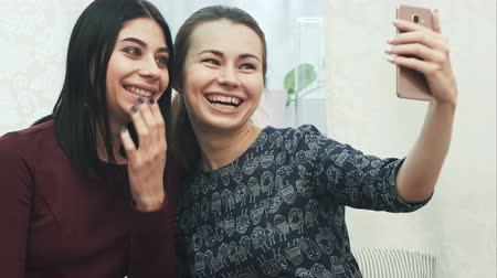 на камеру : Two girls friends taking selfie with smartphone, sitting on sofa at home