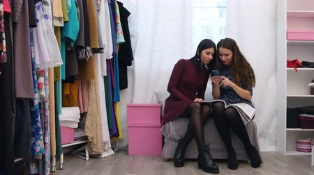 vendedora : Sales assistant in clothing store helping to chose a customer new dress using smartphone and fashion magazine