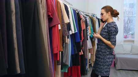 oneperson : Cute young woman talking on her cell phone while checking out some clothes at the store Stock Footage