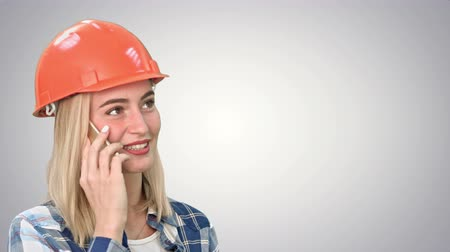 background young : Beautiful happy woman in orange hardhat have a phone call via smartphone and smiling on white background.