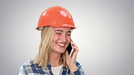 mimar : Beautiful female engineer in hardhat calling via cellphone on white background.