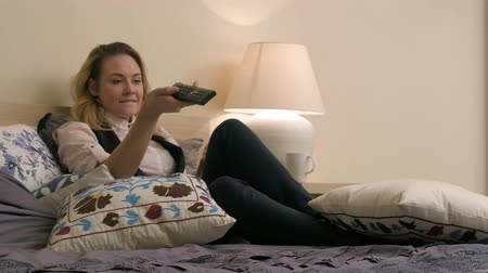 novela : Young blond woman lying on the bed, using smartphone and watching TV