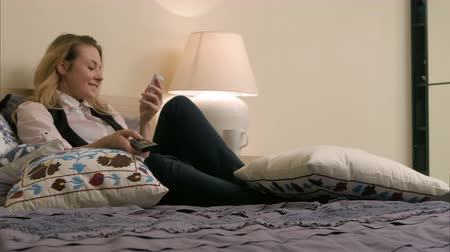 novela : Young beautiful woman lying on the bed, turning on TV channels and using smartphone at home Stock Footage