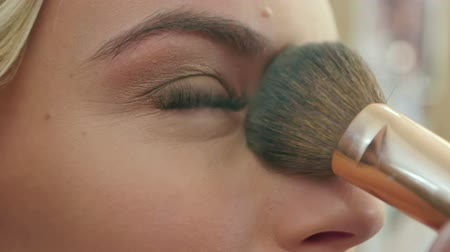 vurgulayıcı : Applying blush makeup with brush to cheekbones of young woman Stok Video
