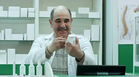 gyógyszerész : Smiling doctor holding up a bottle of tablets advacing it to a customers looking to a camera