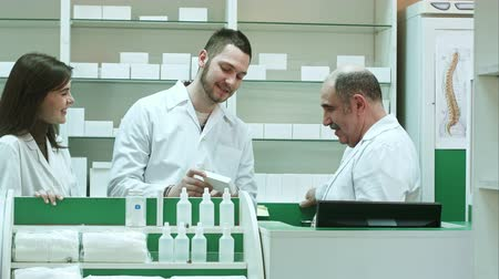 gyógyszerész : Friendly medical team in lab coat discussing new pills in pharmacy