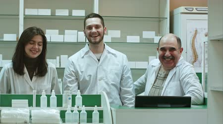 продавщица : Three competent pharmacists laughing in a pharmacy looking at camera Стоковые видеозаписи