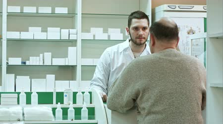 med : Young pharmacist and senior man customer with drug and prescription at drugstore Stock Footage