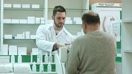 med : Young pharmacist giving drug to senior man customer and taking payment in dollars at drugstore