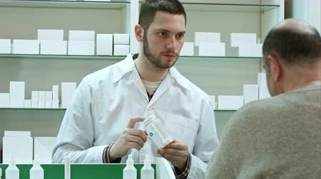 med : Young pharmacist advicing pills senior man customer at drugstore