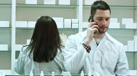 boticário : Female and male pharmacists working in pharmacy, talking via smart phone and checking pills Vídeos
