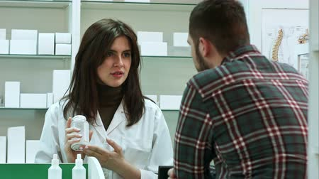 консультация : Young female pharmacist suggesting medical drug to male buyer in pharmacy drugstore