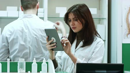 supervising : Female pharmacist with digital tablet searching for medication