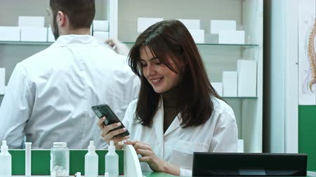 gyógyszerész : Young female pharmacist texting messages using mobile phone, smiling and talking to her male colleauge