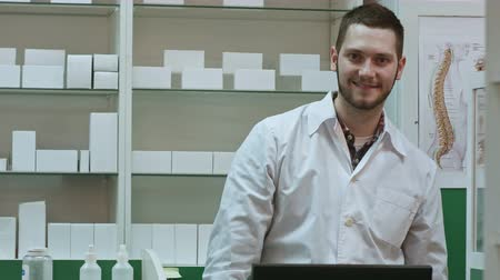 okey : Smiling male pharmacist in white coat showing thumbs up and okey hands gesture