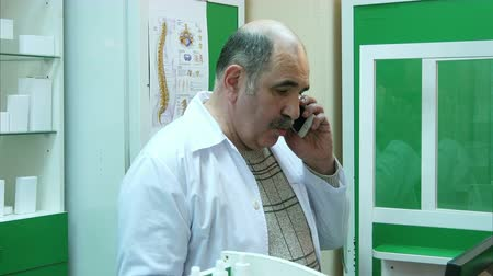 dispanser : Senior pharmacist talking on mobile phone while checking prescription in pharmacy