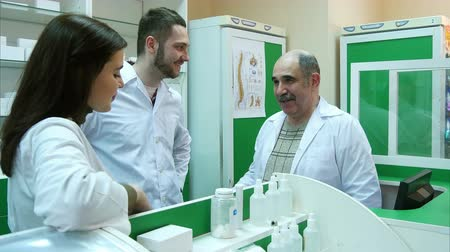 gyógyszerész : Positive team of pharmacist talking and smiling at the hospital pharmacy Stock mozgókép