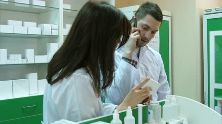 dispanser : Young male pharmacist talking on mobile phone while checking prescription in pharmacy Stok Video