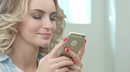 buying online : Happy young blond woman is sitting in a beauty salon and using a smartphone
