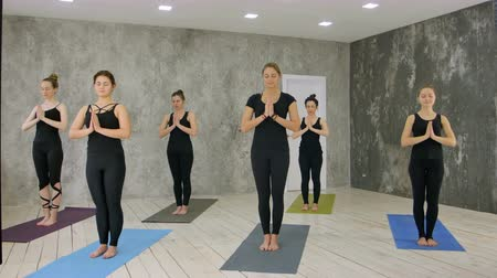 retiro : Female trainer with class standing in namaste pose at yoga class