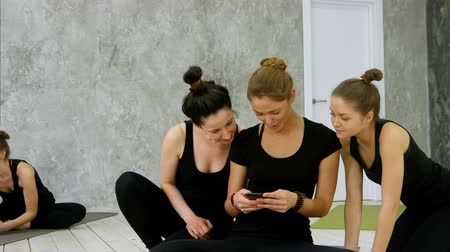 make friends : Three young women using digital cell phone after workout at yoga class