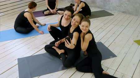 make friends : Three young women making selfie via smartphone at yoga class