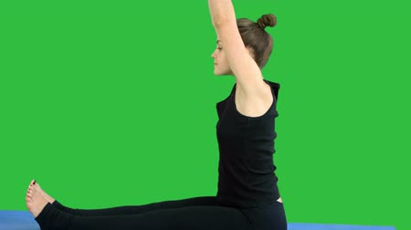 tvarování : Young woman stretching leg on mat, practicing yoga on a Green Screen, Chroma Key