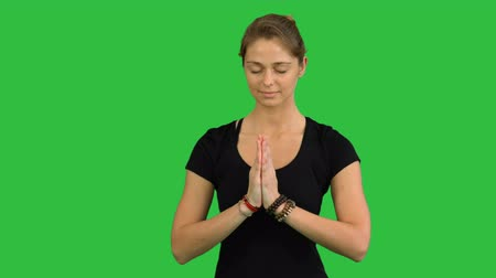 close cropped : Woman with Namaste Mudra gesture meditating with closed eyes on a Green Screen, Chroma Key
