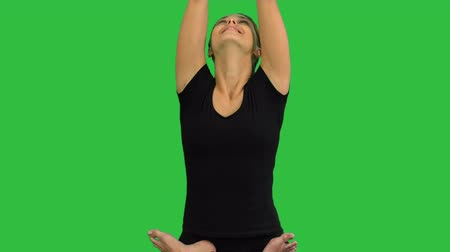 mala : Young woman sitting in lotus yoga pose practicing meditation on a Green Screen, Chroma Key