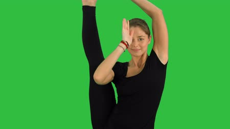 esneme : A yoga position for balance and stretching, woman practicing Utthita Hasta Padangustasana on a Green Screen, Chroma Key
