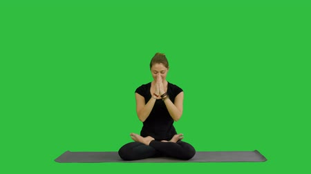 crossed : Young woman practicing yoga, sitting in a lotus position, meditating with closed eyes on a Green Screen, Chroma Key