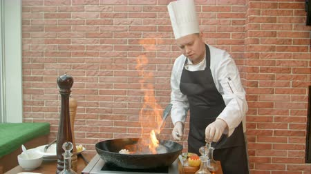 seafood dishes : Chef preparing seafood in pan with alcohol in big flame