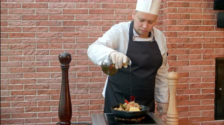 мастер : Chef finishing the dish, putting oil to a plate
