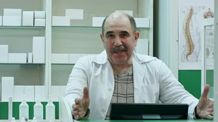 representante : Senior pharmacist talk to a camera presenting medicine advice medical treatment in pharmacy shop