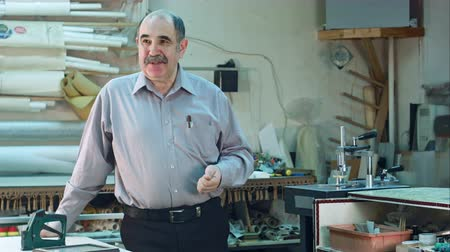 mend : Portrait of a senior male business owner behind the counter of his frame workshop, standing and talking to a camera Stock Footage