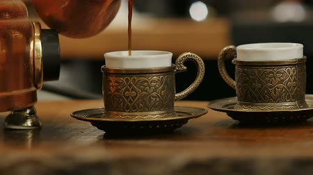 grille : Hand pouring black coffee from turk into coffee cup
