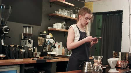 employee : Female barista taking pictures of prepared cofee with smartphone