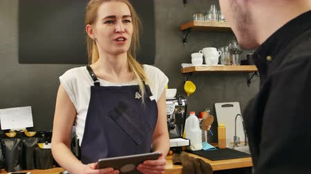 use computer : Portrait of a gorgeous female barista taking the order of a customer with a tablet computer and smiling