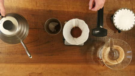 официант : Hand drip coffee , barista pouring water on coffee ground with filter