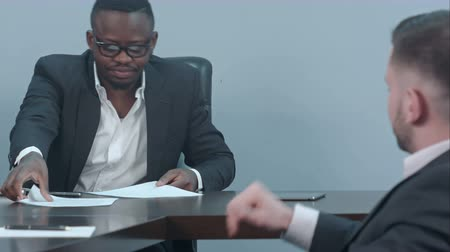 afroamerican : Black businessman signs a contract and gives papers to a partner