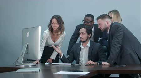conference table : Group of multiracial business people around the conference table looking at laptop computer and talking to one another Stock Footage