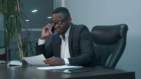 afroamerican : Afro-american businessman examining charts and talking on the phone Stock Footage