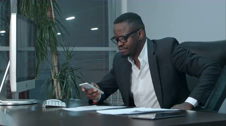 связать : Afro-american businessman reading emails on his smartphone and texting answers Стоковые видеозаписи