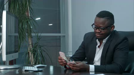 miktar : Afro businessman counting cash, sitting at desk in office